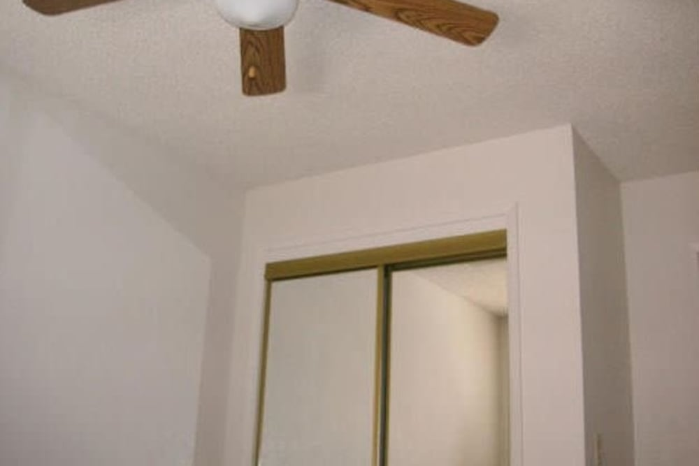 Bedroom with closet and ceiling fan at Olympus Court Apartments in Bakersfield, California