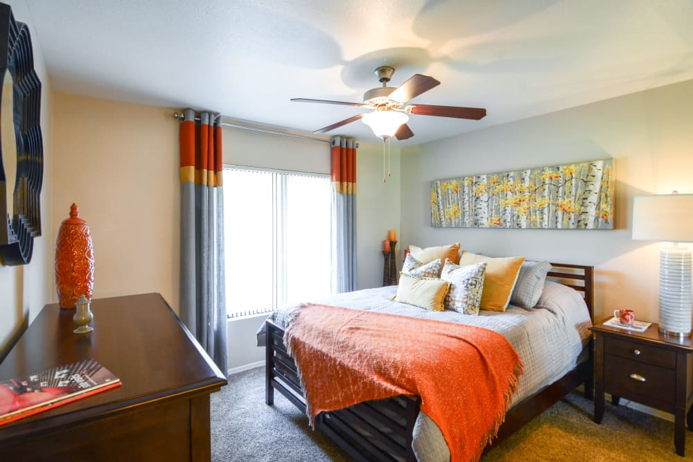 Bright bedroom with orange accents at The Palms on Scottsdale in Tempe, Arizona