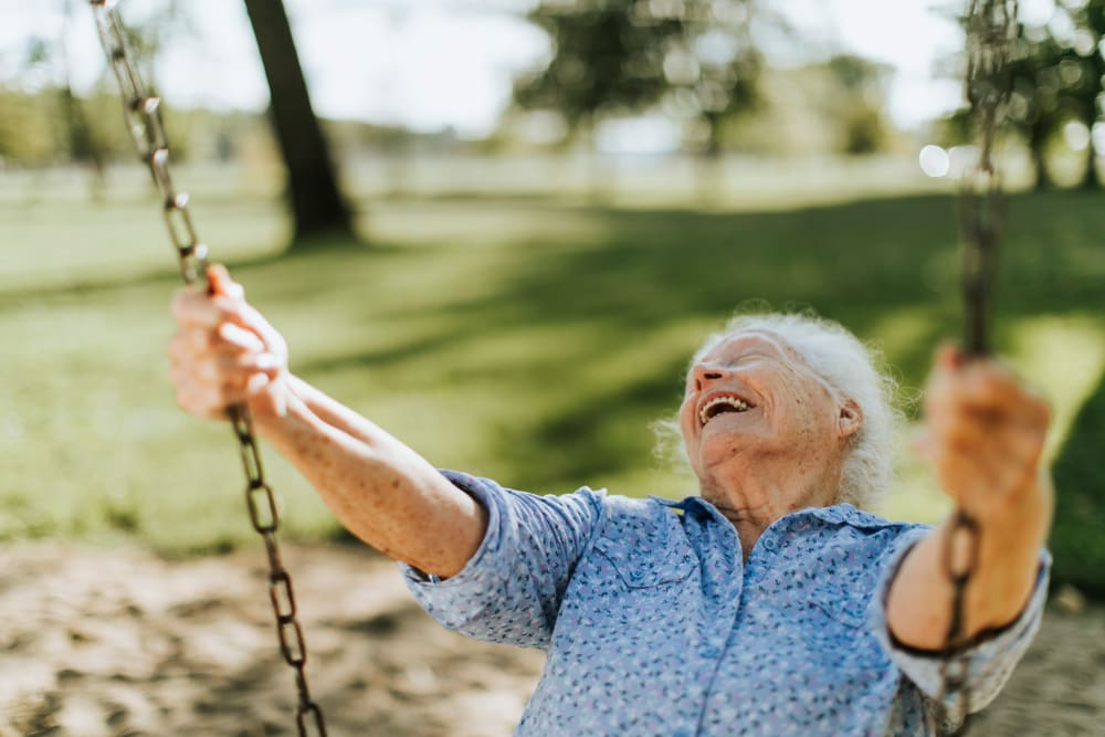 Resident smiling while swinging on swing at Arlington Place Oelwein in Oelwein, Iowa