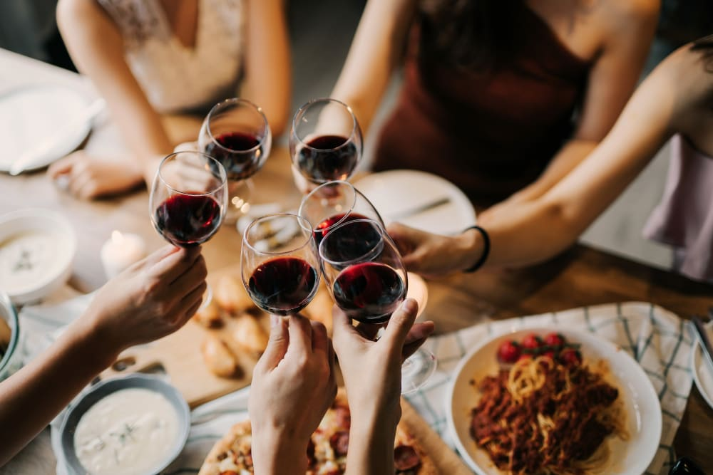 Friends eating a sumptuous meal and raising their wine glasses to toast the good life at a restaurant near Portside Ventura Harbor in Ventura, California