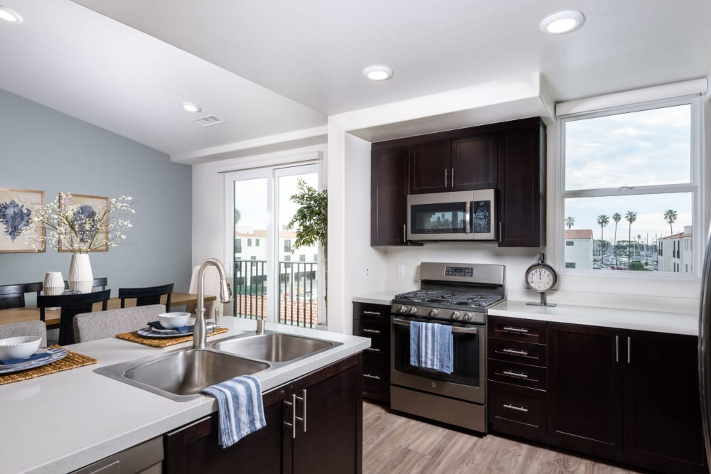 Gorgeous gourmet kitchen with espresso wood cabinetry and stainless-steel appliances in a model home at Portside Ventura Harbor in Ventura, California