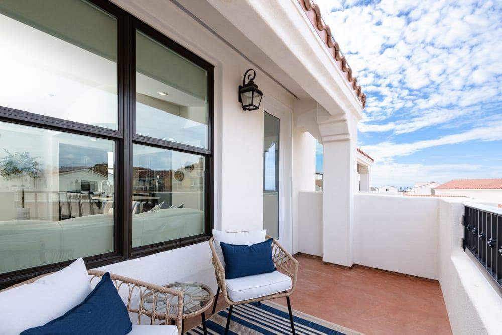 Comfortably furnished private balcony outside a model home at Portside Ventura Harbor in Ventura, California
