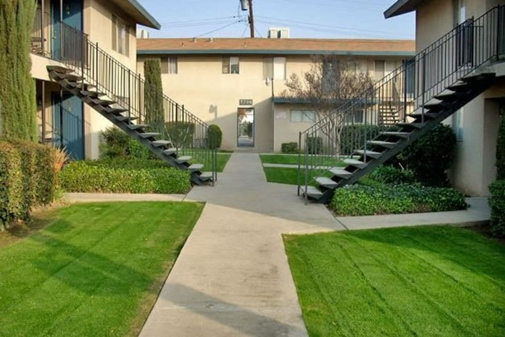 View of the exterior landscape and stairwells at Highland View Court in Bakersfield, California