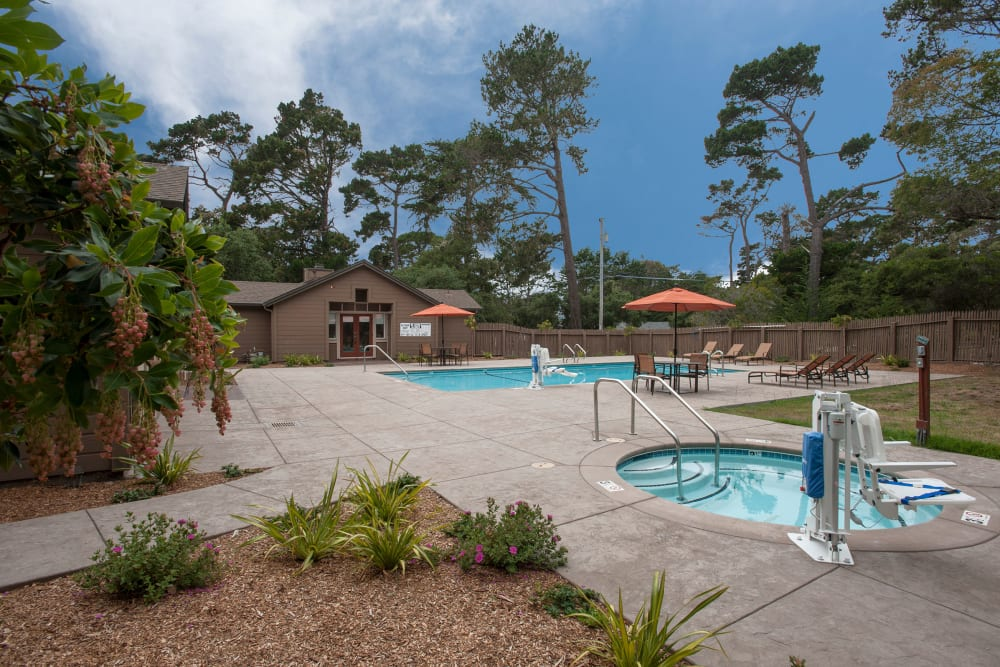 Relaxing swimming pool and hot tub outside at Seventeen Mile Drive Village Apartment Homes in Pacific Grove, California