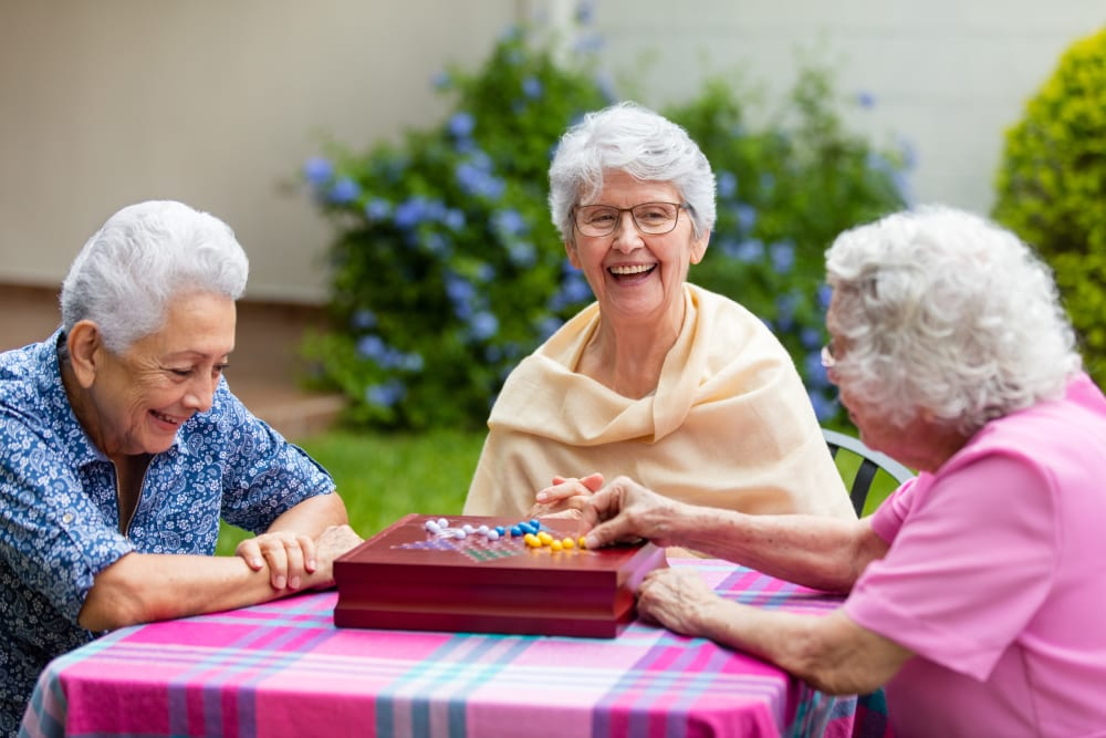 Resident friends playing a game outside at Merrill Gardens.