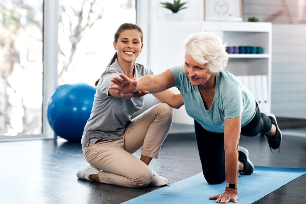 Caregiver assisting a resident who is doing yoga at a Jaybird Senior Living community