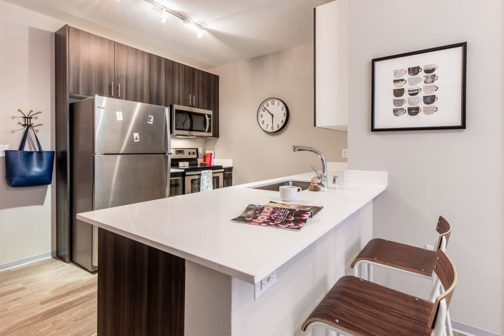 Fully equipped kitchen with wood style flooring at evolve on Main in Pullman, Washington