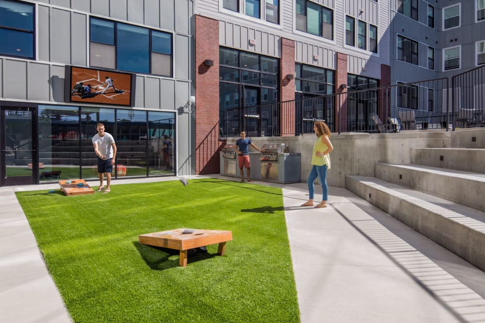Community courtyard with cornhole boards at HERE Kansas in Lawrence, Kansas