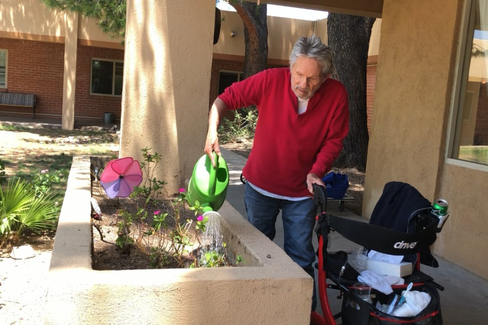 Watering plants at Woodland Palms Memory Care in Tucson, AZ