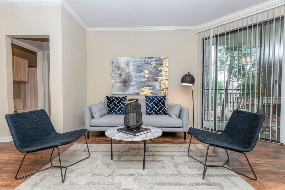 Model living room with blue accent chairs and hardwood floors at The Lyndon in Irving, Texas