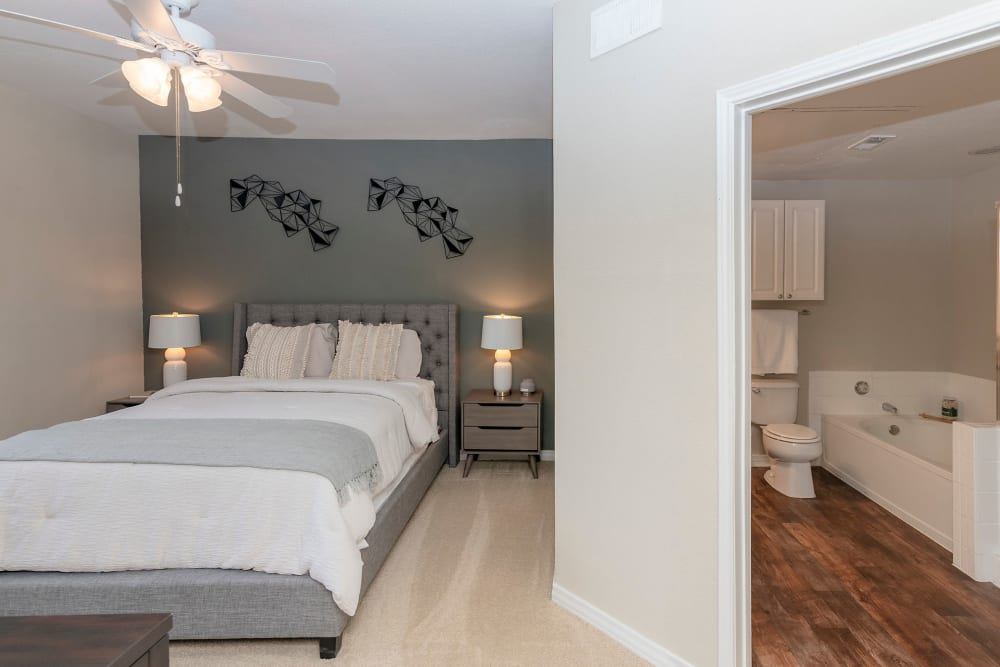 Well lit model bedroom with ceiling fan at The Lyndon in Irving, Texas