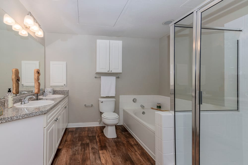 Large model bathroom with glass shower and adjacent oval tub at The Lyndon in Irving, Texas