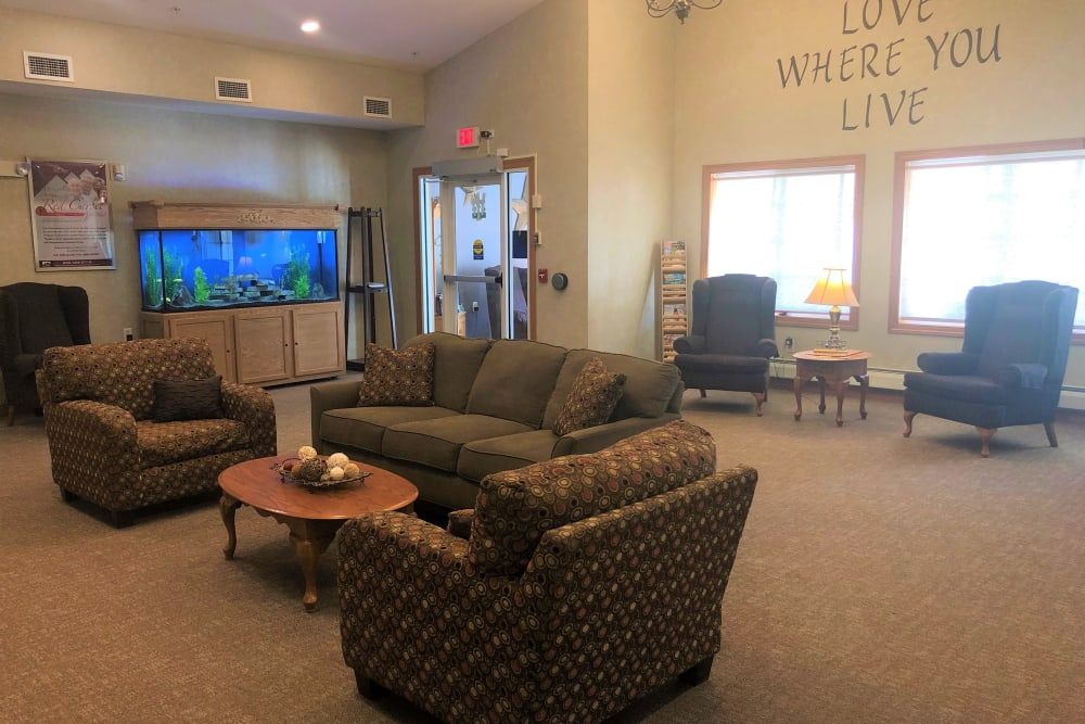 Large lounge with a bright fish tank in it at Arlington Place Oelwein in Oelwein, Iowa