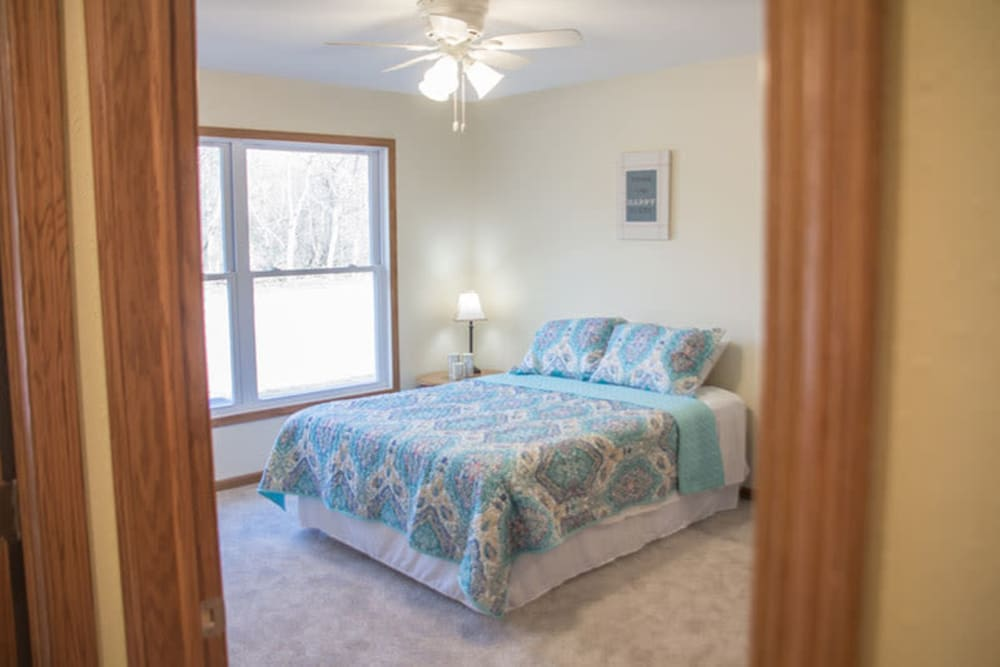 Bedroom with a large window in a townhome at Arlington Place Oelwein in Oelwein, Iowa