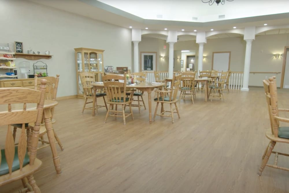 Large dining hall with bright hardwood flooring at Arlington Place Oelwein in Oelwein, Iowa
