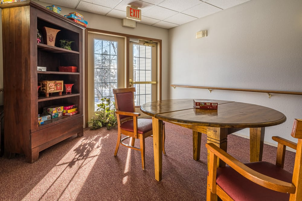 Sunlit game room with a central circular table at Traditions of Owatonna in Owatonna, Minnesota