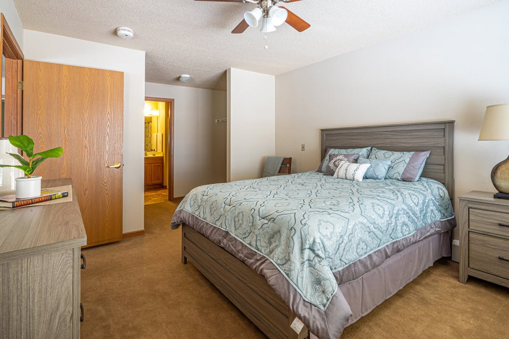 Brightly lit bedroom in an apartment at Traditions of Owatonna in Owatonna, Minnesota