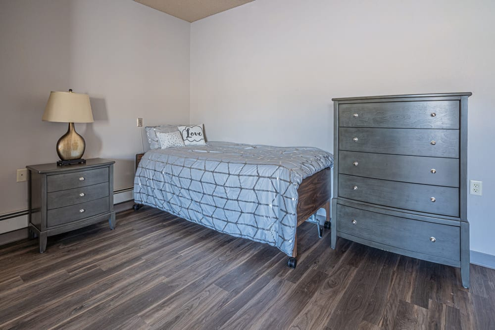 Single person bed next to a nightstand and a dresser at Traditions of Owatonna in Owatonna, Minnesota