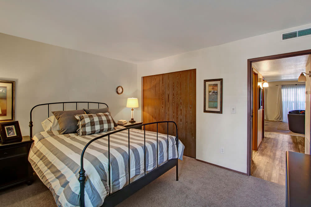 Model bedroom with bedside lamps and closet at Overlook Point Apartments in Salt Lake City, Utah