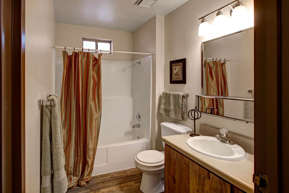 Model bathroom with large vanity mirror and oval tub at Overlook Point Apartments in Salt Lake City, Utah