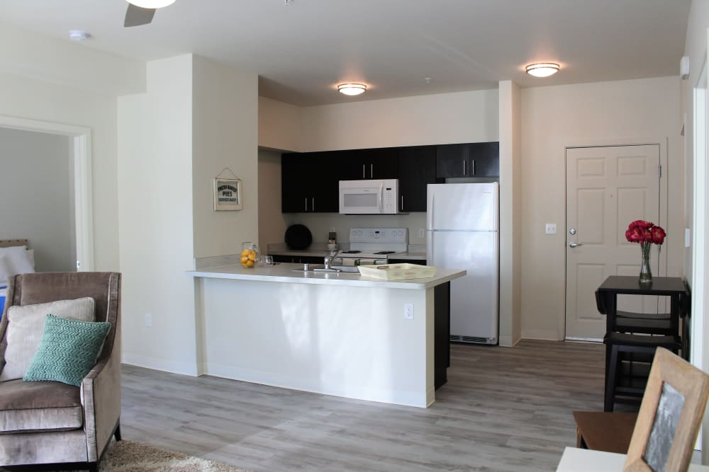 Open concept layout with Hardwood floors and kitchen bar at LARC at Burien in Burien, Washington