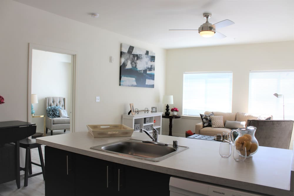 Open concept layout with view of living room from kitchen bar at LARC at Burien in Burien, Washington