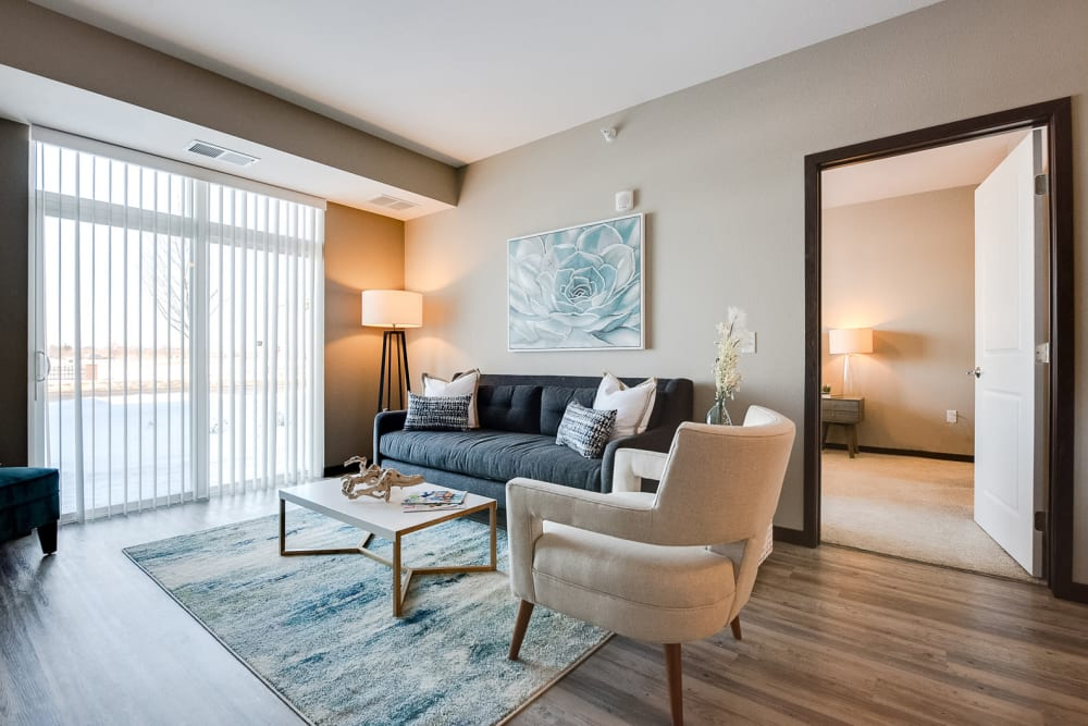 Contemporary living room with wood-style flooring at Remington Cove Apartments in Apple Valley, Minnesota