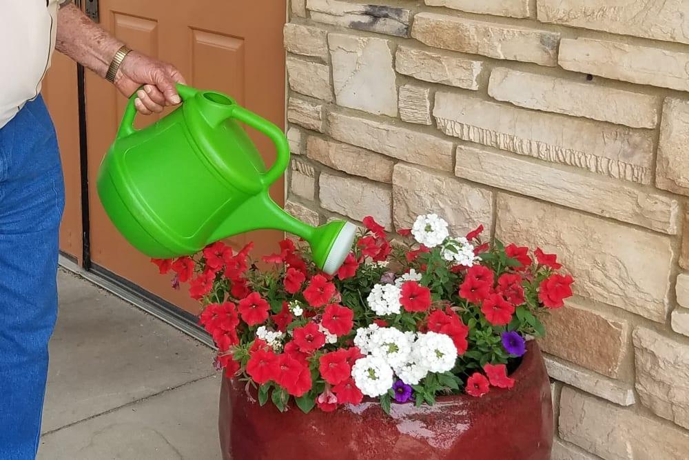 Resident watering plants and gardening at Prairie Hills Cedar Rapids in Cedar Rapids, Iowa.