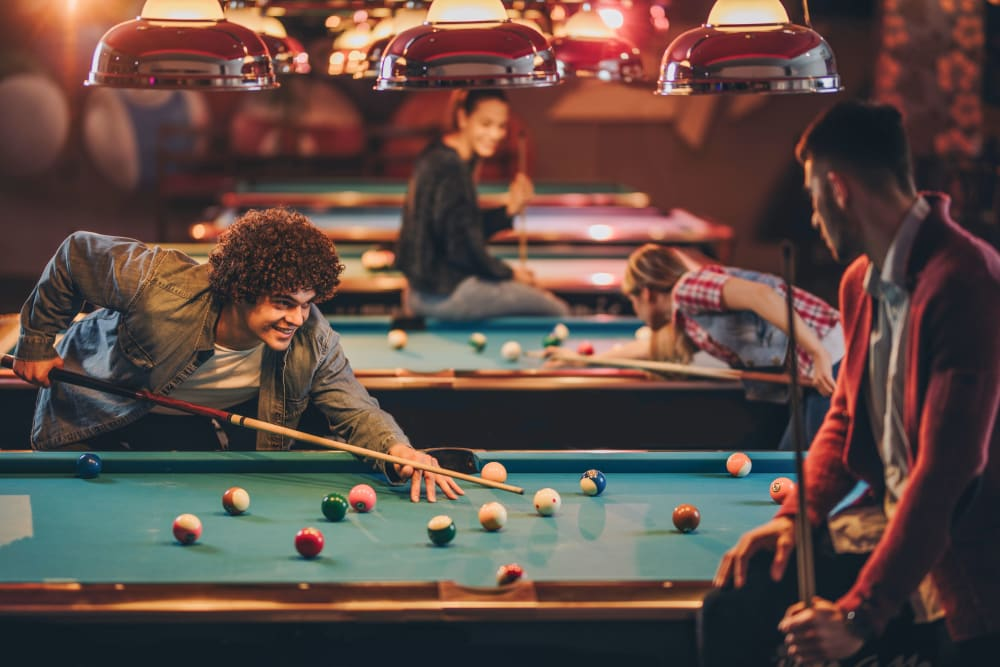 Friends playing pool near RISE at State College in State College, Pennsylvania
