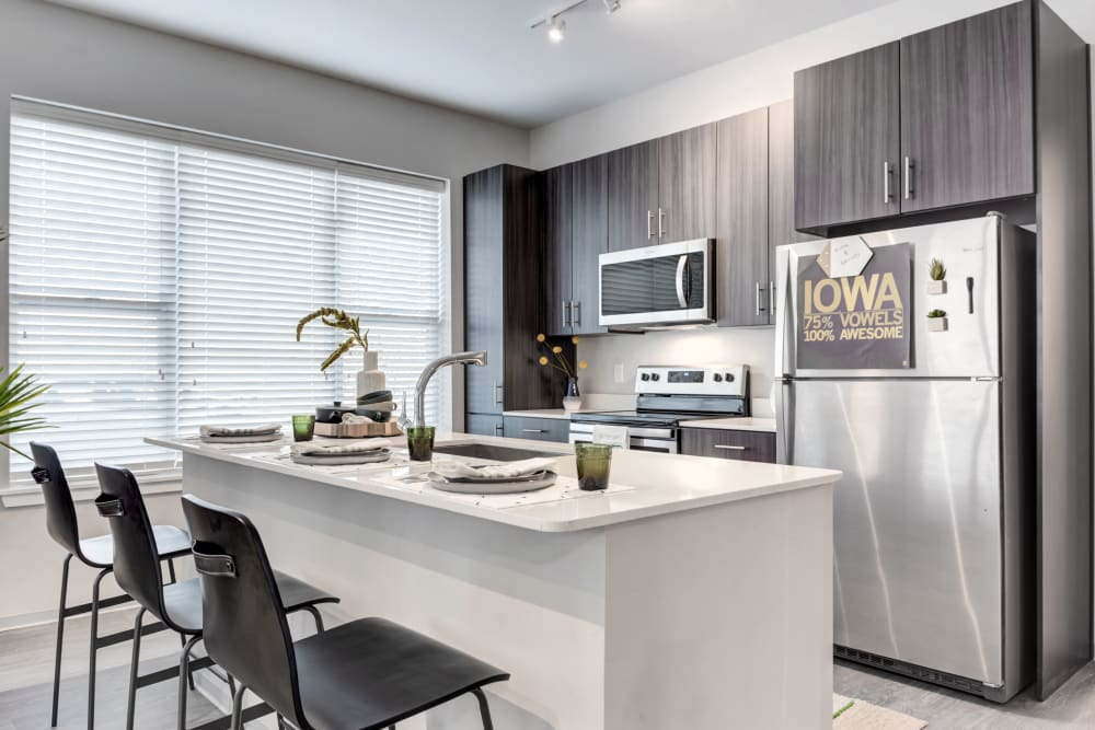 Kitchen with stainless steel appliances at LATITUDE at River Landing in Coralville, Iowa