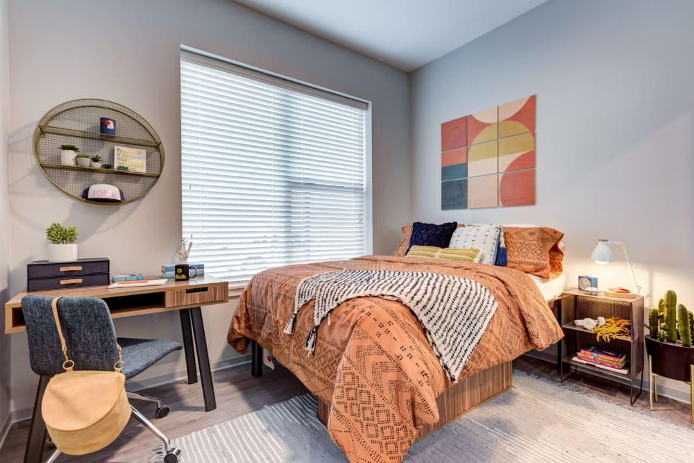 Bedroom with a study space at LATITUDE at River Landing in Coralville, Iowa