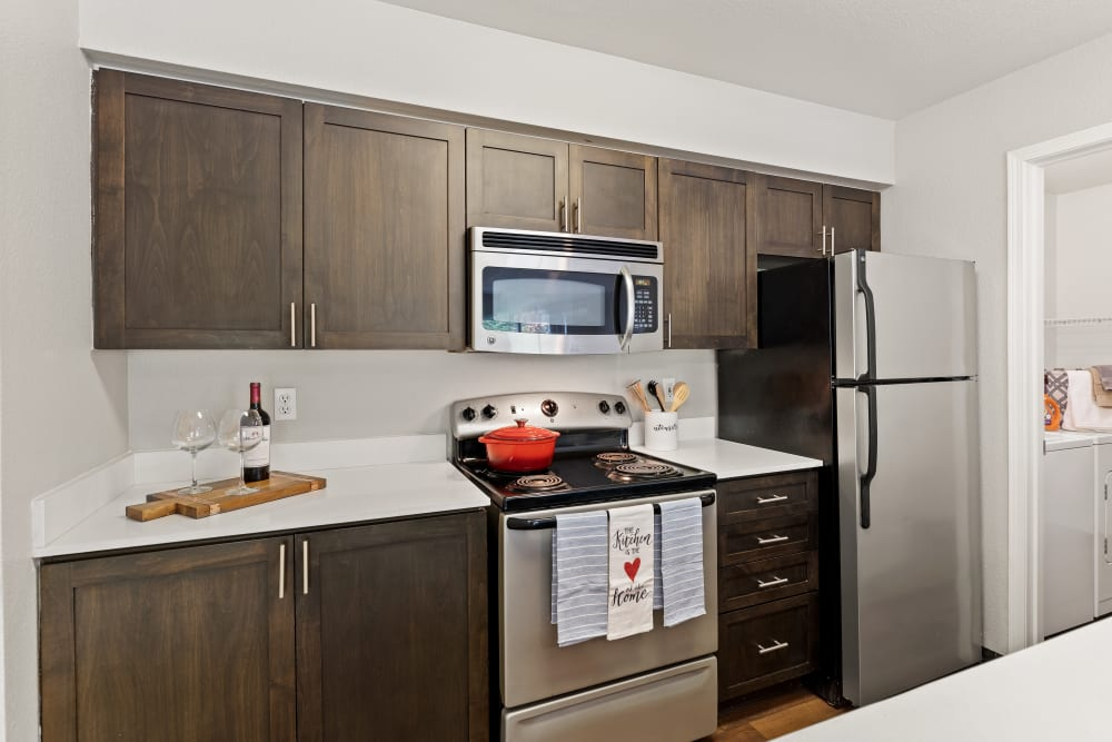 A kitchen with brown cabinets and a bar area at HighGrove Apartments in Everett, Washington