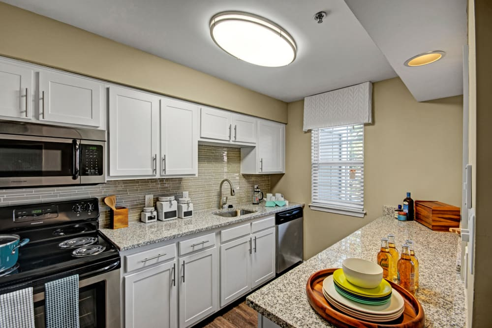 Kitchen at Exton Crossing in Exton, Pennsylvania features white cabinets and black appliances
