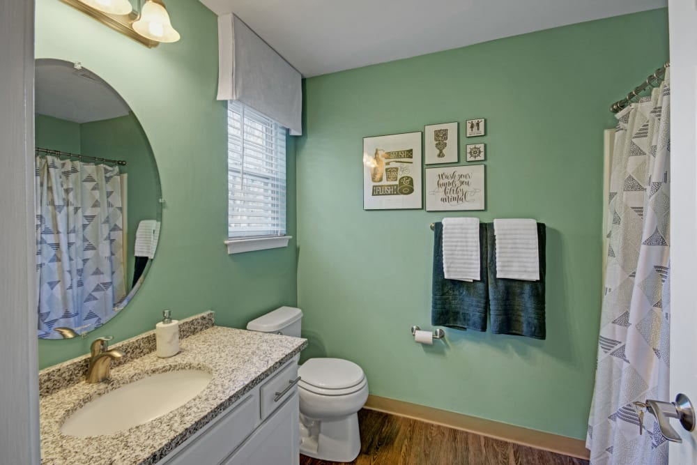 Bathroom with mint green walls and circular vanity mirror at Exton Crossing in Exton, Pennsylvania