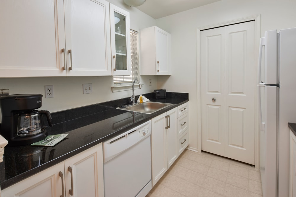 Model kitchen with black countertops and white wood cabinets at Citation Club in Farmington Hills, Michigan