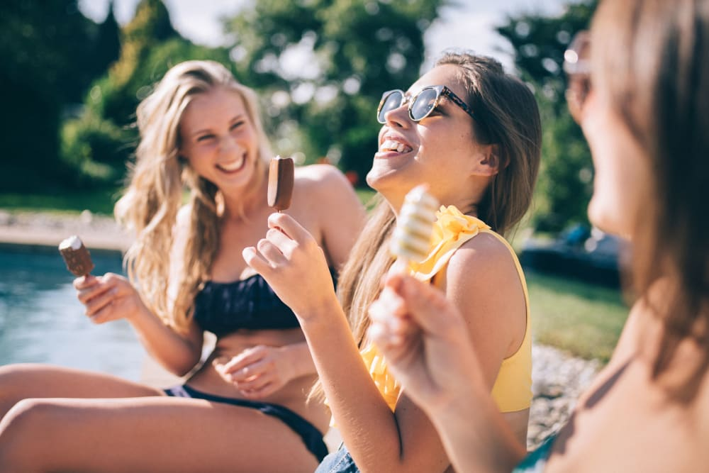 Residents relaxing by the pool with ice cream at The Cloisters in Miami, Florida