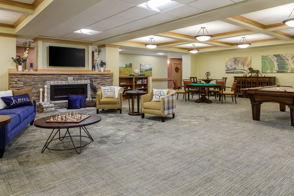 Resident lounge with lots of space, a tv, and a fireplace at Edencrest at Beaverdale in Des Moines, Iowa