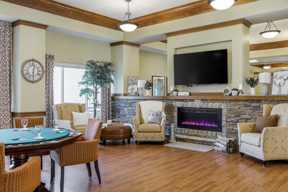 Senior activity lounge with games, a tv, and fireside seating at Edencrest at The Legacy in Norwalk, Iowa