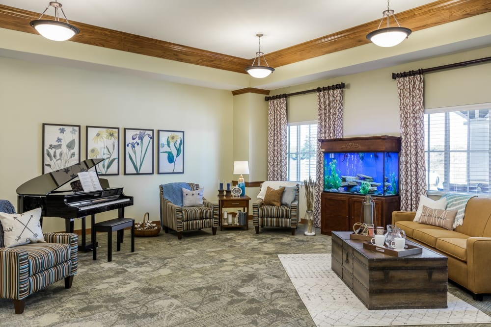 Resident lounge with a bright blue fish tank and a piano at Edencrest at The Legacy in Norwalk, Iowa
