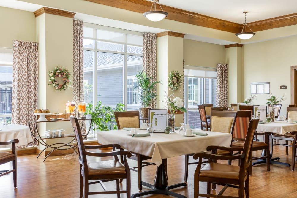 Dining hall with large windows and hardwood floors at Edencrest at The Legacy in Norwalk, Iowa