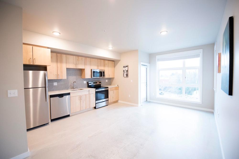Beautiful hardwood flooring in a model home's open-concept kitchen at Brooklyn Yard in Portland, Oregon