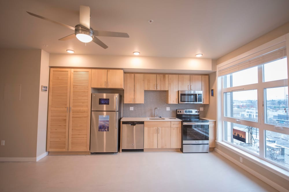 Stainless-steel appliances in a model home's kitchen with gorgeous city views from the large bay windows at Brooklyn Yard in Portland, Oregon