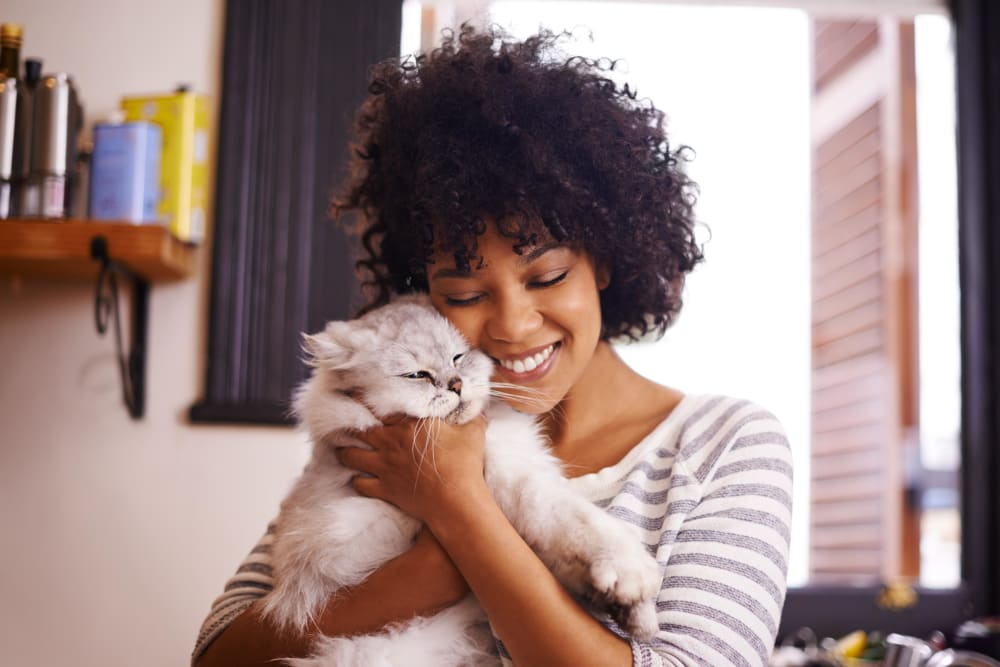 Resident and her cat sharing a loving moment in their apartment home at The Station at River Crossing in Macon, Georgia