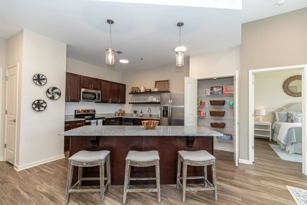 Model home's gourmet kitchen with granite countertops, an island with bar seating, and dark wood cabinetry at The Station at River Crossing in Macon, Georgia