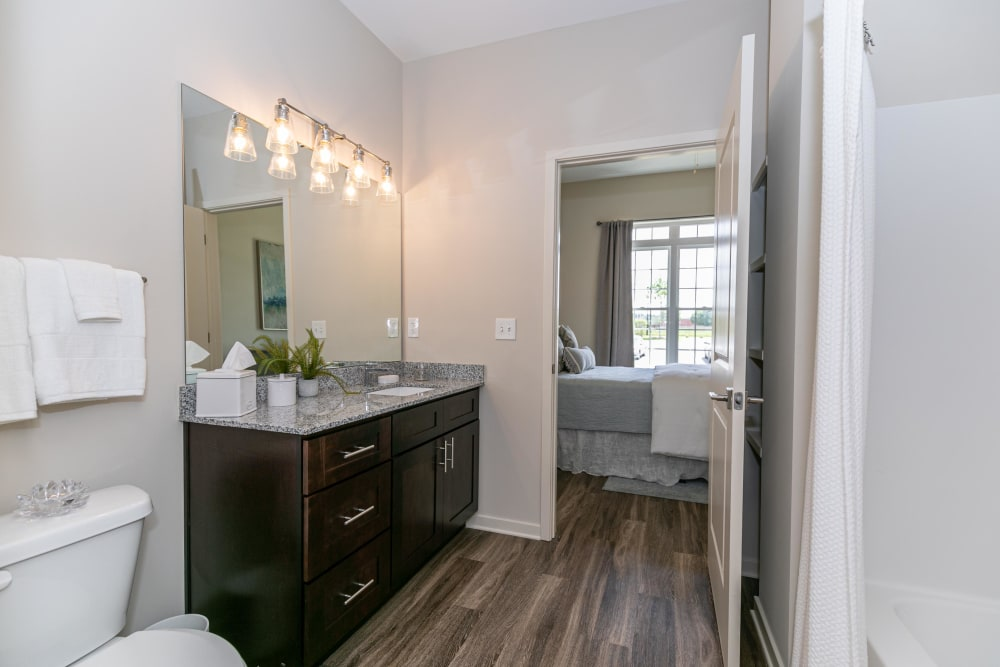 En suite primary bathroom with hardwood floors and a large vanity mirror in a model home at The Station at River Crossing in Macon, Georgia