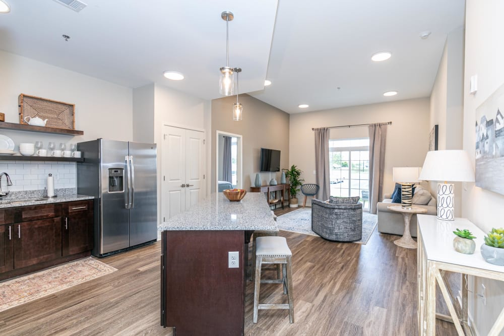 Spacious open-concept floor plan with hardwood flooring and recessed lighting in a model home at The Station at River Crossing in Macon, Georgia