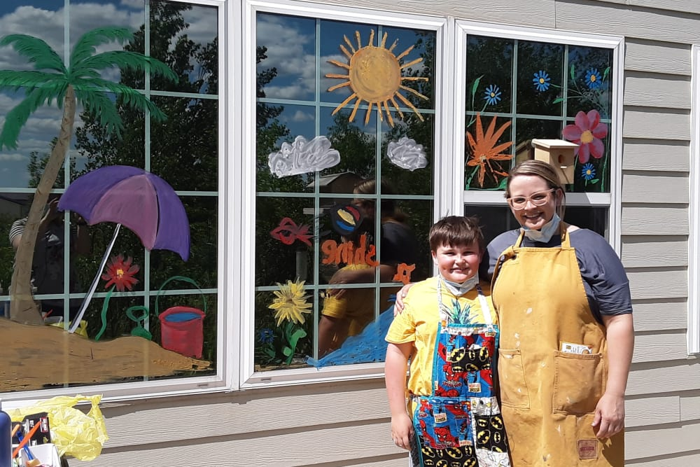 Artist and a young child standing in front of painted windows outside Keelson Harbour in Spirit Lake, Iowa