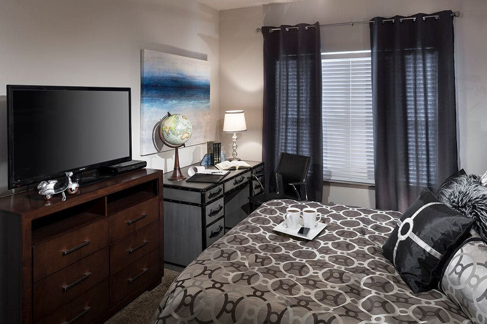 Plush carpeting and a large bay window in a model home's bedroom at Hyde Park at Montfort in Dallas, Texas