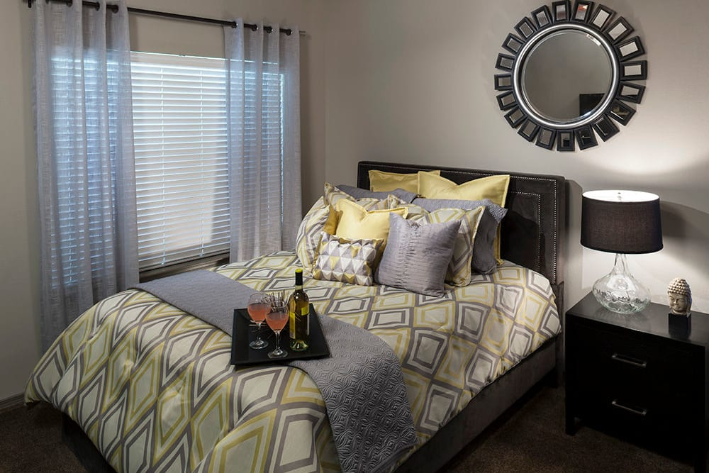Comfortably furnished model apartment's bedroom with draped a window at Hyde Park at Montfort in Dallas, Texas