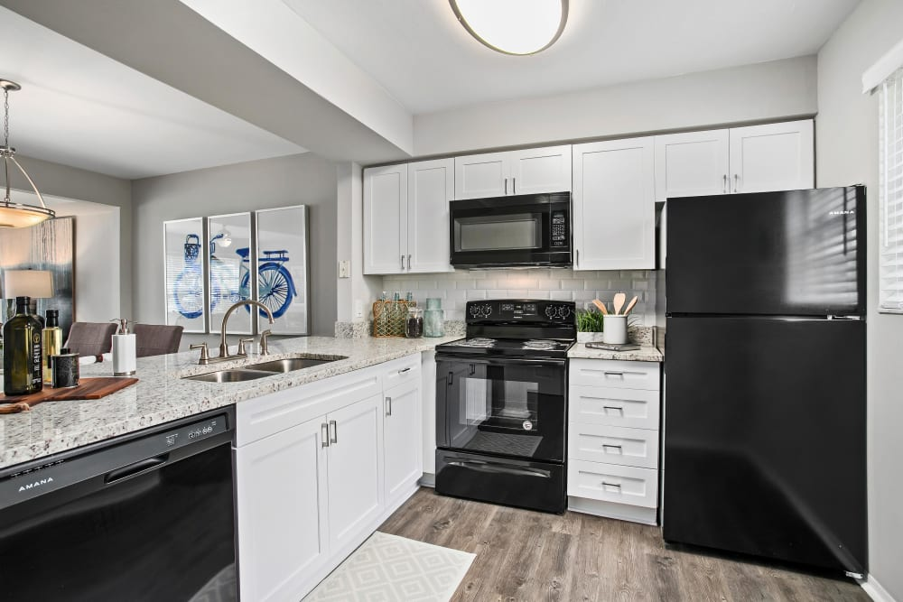 Sleek black appliances and hardwood flooring in a model home's kitchen at The Coast of Naples Florida in Naples, Florida